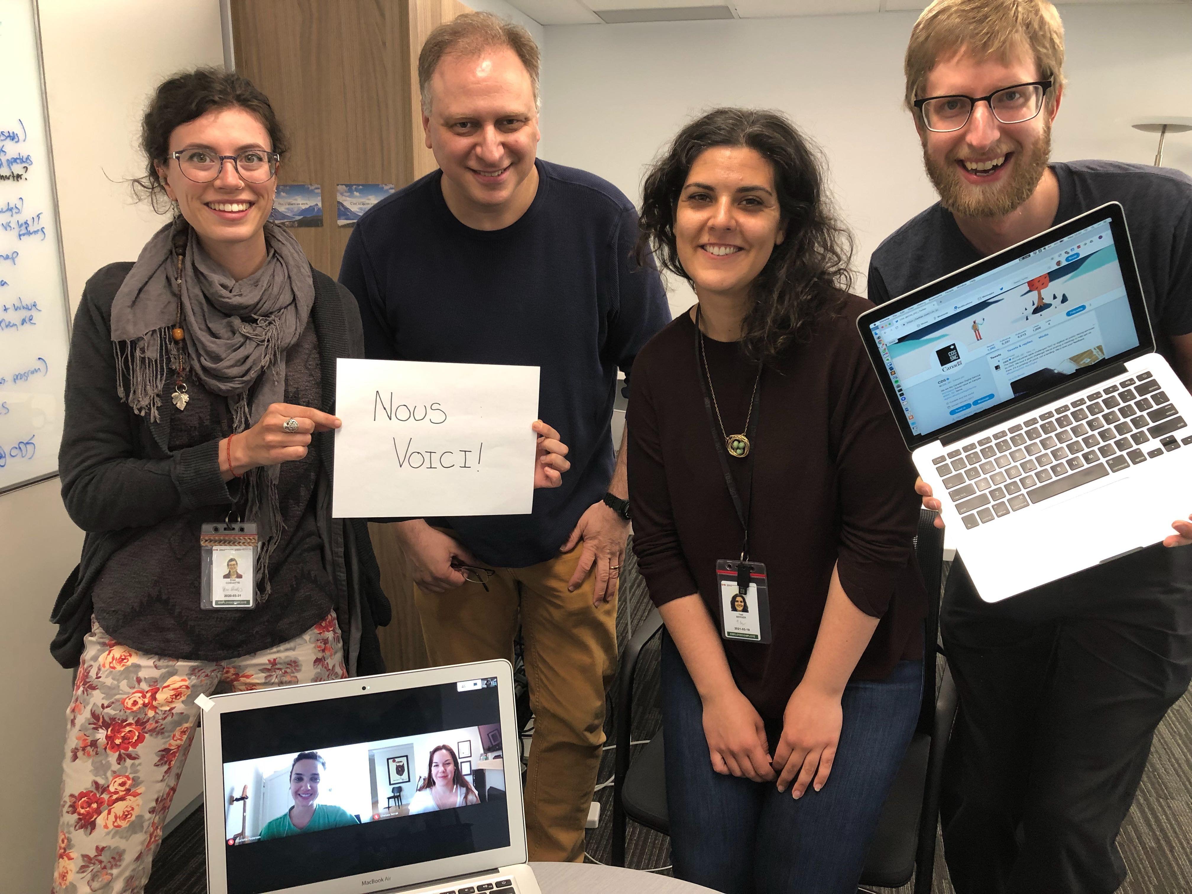 Photo de l'équipe avec une affiche indiquant « Nous voici! » avant le début de l'AMA.