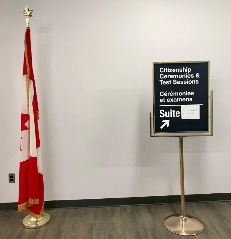 Un drapeau canadien et un signe qui montre où les cérémonies et les examens de citoyenneté ont lieu.