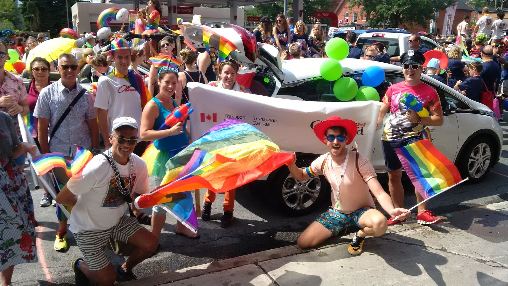 Un groupe de fonctionnaires du Secrétariat du Conseil du Trésor et de Transports Canada au défilé de la fierté gaie d'Ottawa, y compris James, tenant des bannières et des drapeaux de la fierté.