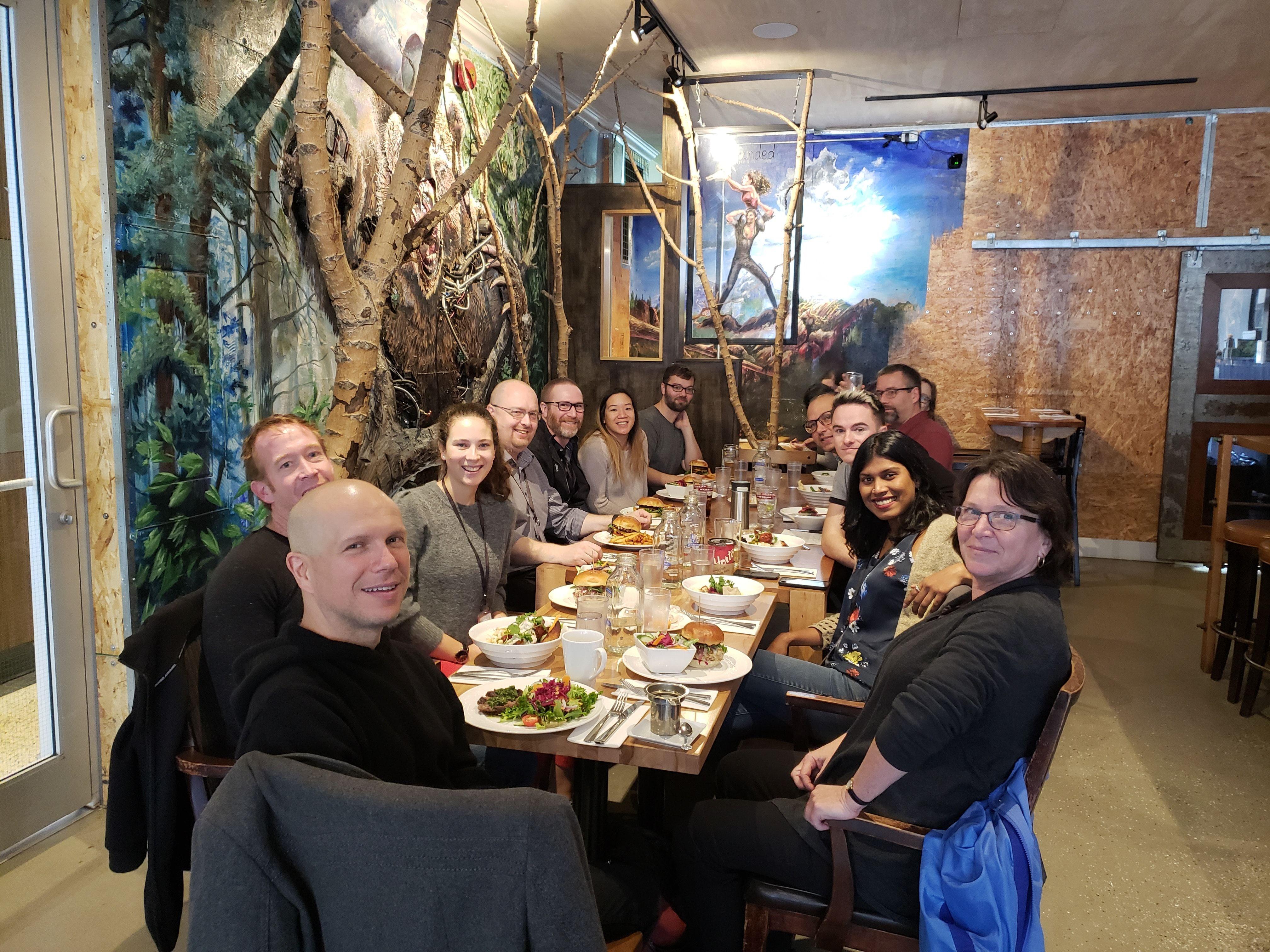 Les membres de l'équipe, assis autour d'une grande table dans un restaurant, sourient pour une photo.