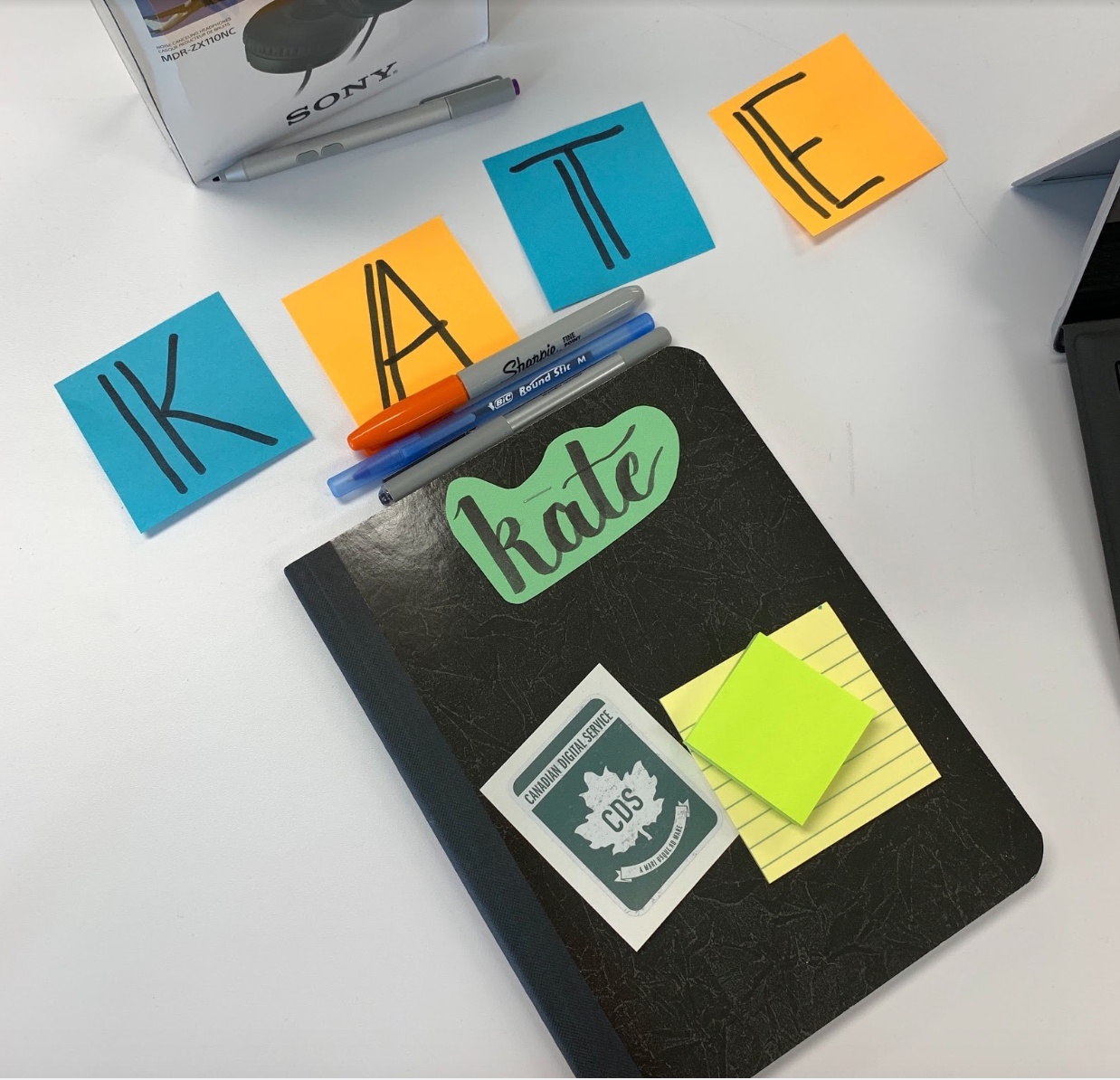 A photo of Kate's work station on her first day, specifically four sticky notes that read KATE, three pens, a notebook with Kate's name, a CDS sticker, and sticky notes.